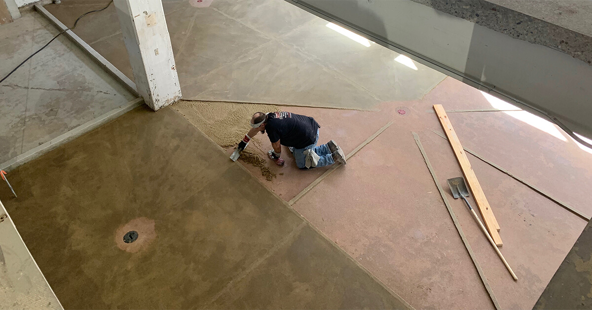 A resinous flooring installer slopes the floor to drains.